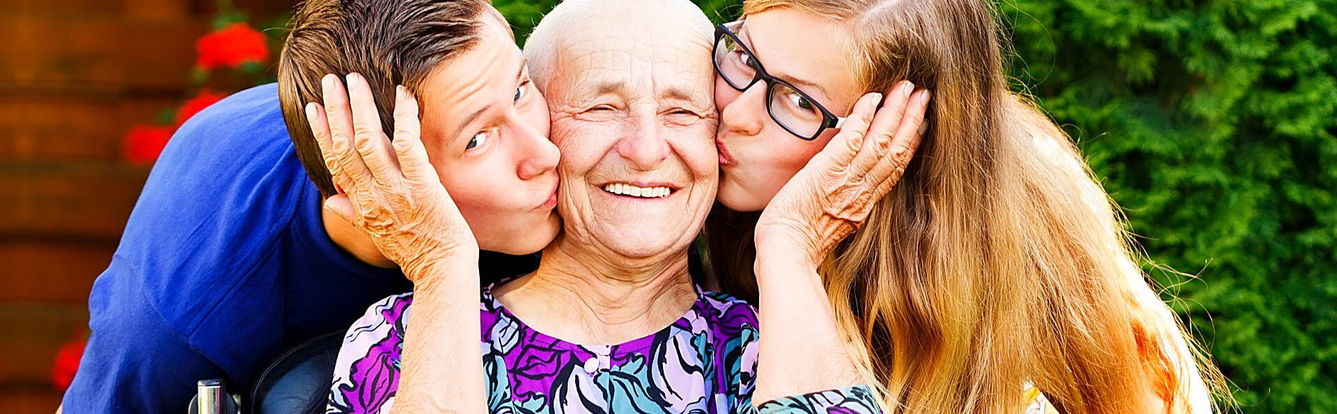 two teenagers kissing their happy grandmother